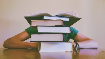 Person versteckt sich hinter Bücherstapel