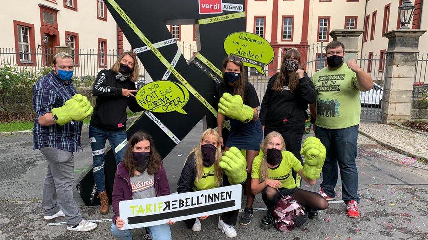 Aktive der ver.di Jugend Leipzig Nordsachsen stehen kämpferisch vor Kampagnenmotiv